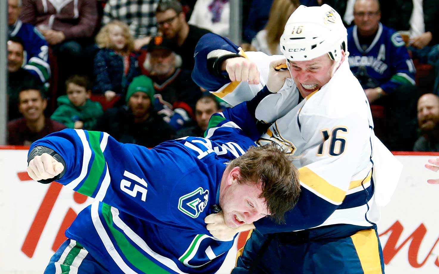 Derek Dorsett of the Vancouver Canucks and Cody Bass of the Nashville Predators fight during their game at Rogers in Vancouver.