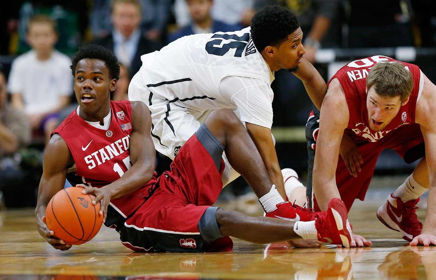 Stanford guard Marcus Allen looks to pass after picking up a loose ball in a scramble with Colorado guard Dominique Collier and Stanford center Grant Verhoeven in Boulder, Colo.
