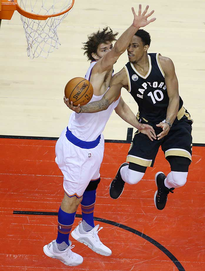 DeMar DeRozan floats by Robin Lopez as the Toronto Raptors play the New York Knicks  at the  Air Canada Centre in Toronto.