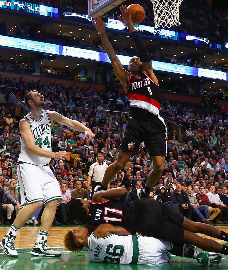 Gerald Henderson of Portland trips over Ed Davis and Marcus Smart of the Boston Celtics.