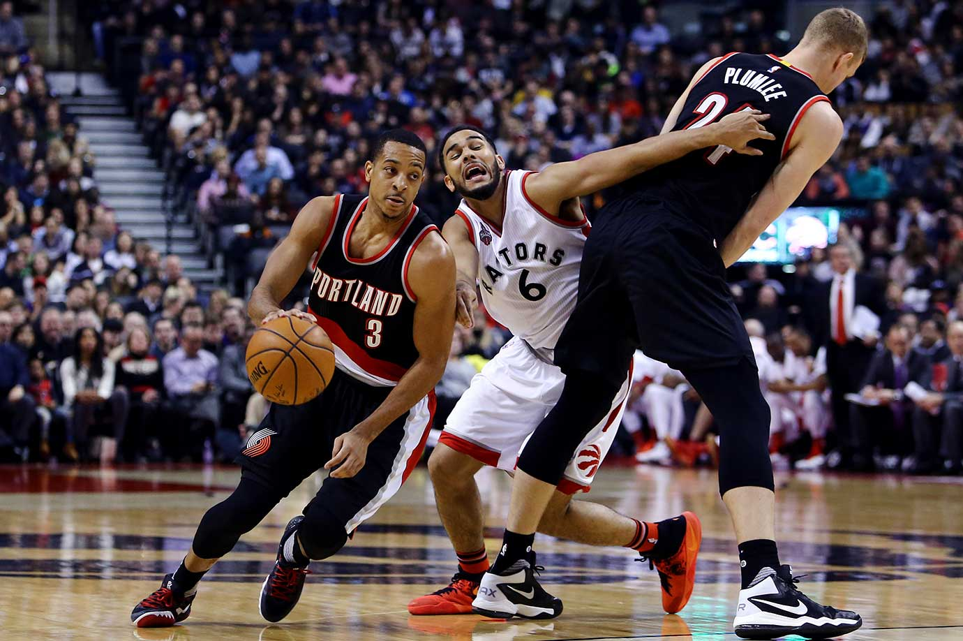 CJ McCollum of Portland dribbles the ball as Cory Joseph of Toronto is screened.