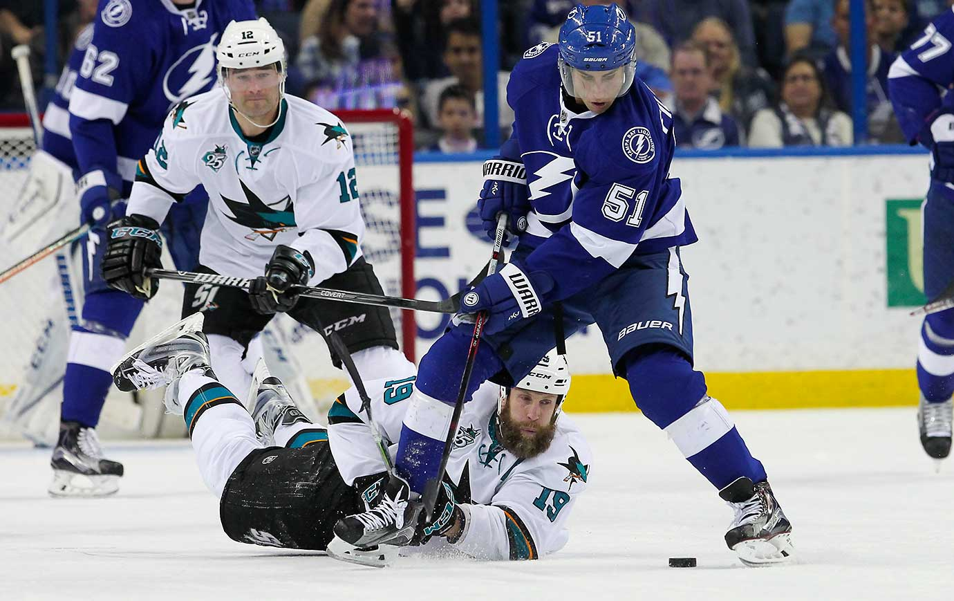 Joe Thornton of San Jose tries to knock the puck away from Valtteri Filppula (51) of Tampa Bay as he lays on the ice.