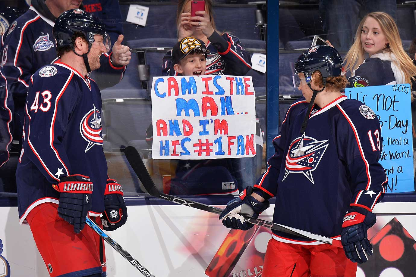 Scott Hartnell, left, and Cam Atkinson of the Columbus Blue Jackets read a sign held by a young fan during warmups.