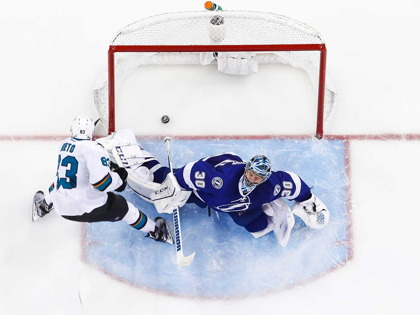 Matt Nieto of San Jose Sharks shoots the puck into the net against an outstretched goalie Ben Bishop of Tampa Bay.