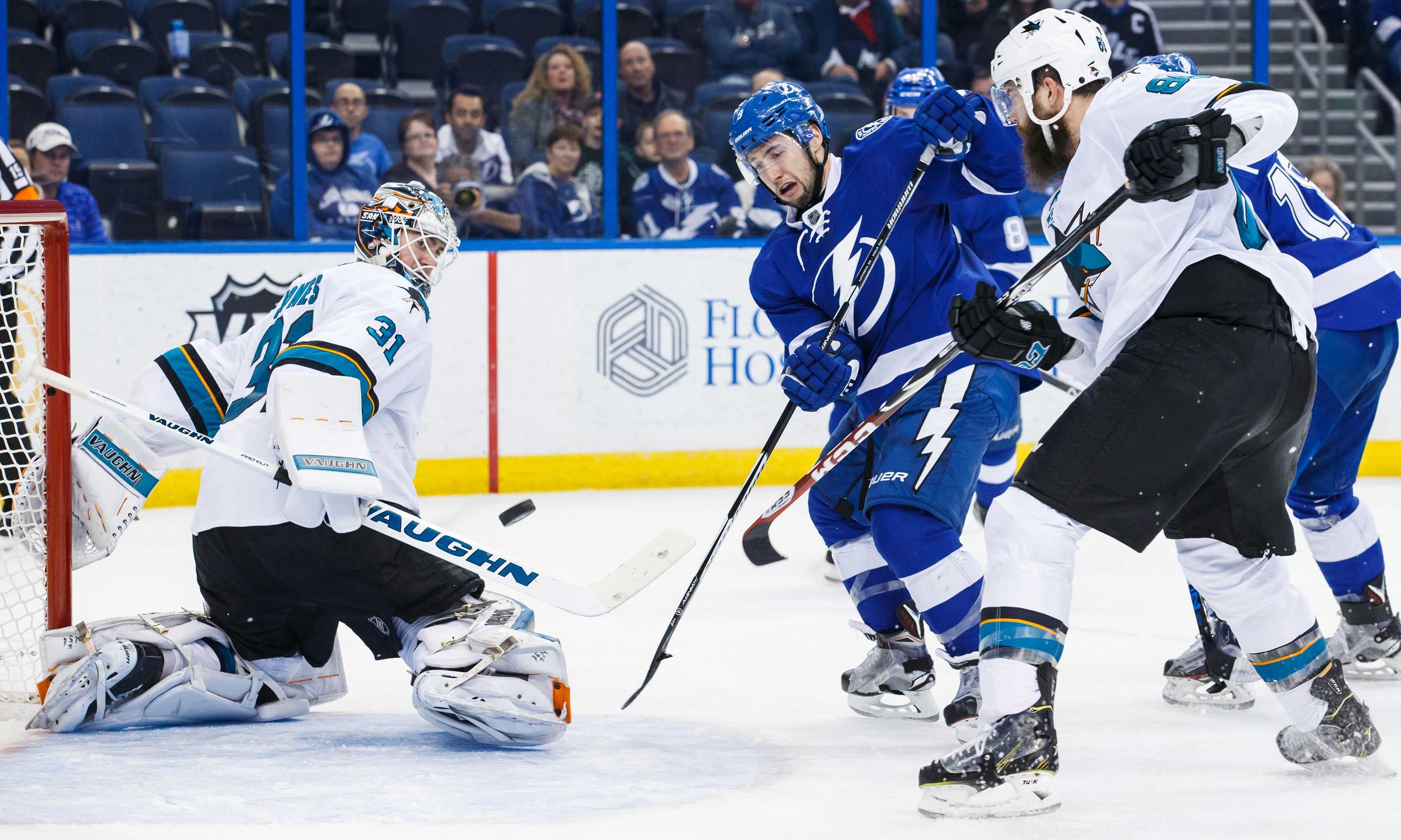 Tyler Johnson (No. 9) of Tampa Bay battles for the puck with Brent Burns next to San Jose goalie Martin Jones.