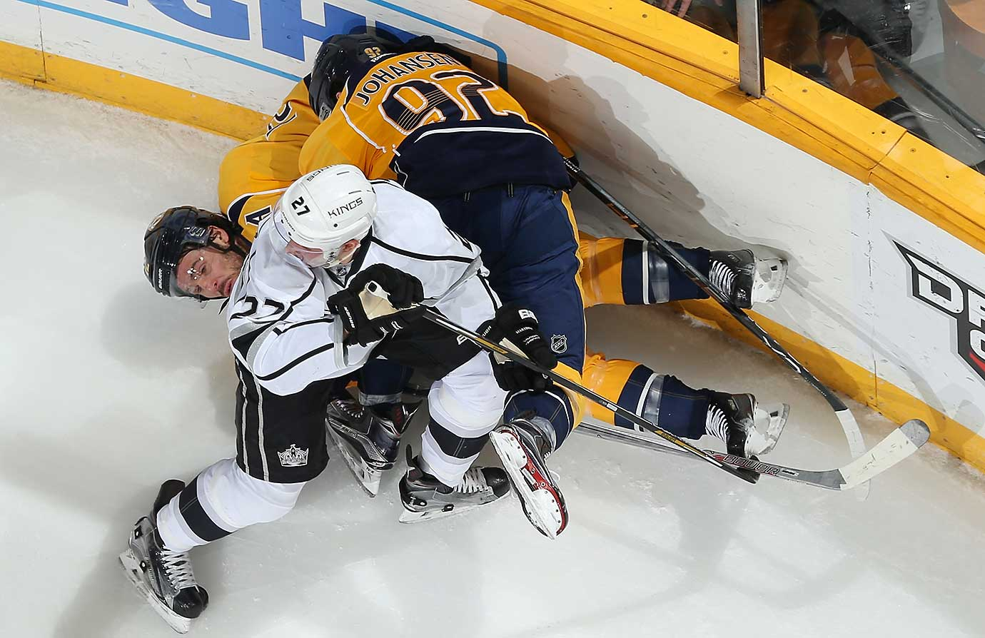 Alec Martinez of the Los Angeles Kings checks Ryan Johansen on to Mike Fisher of the Nashville Predators.