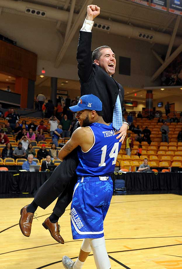 Head coach Nick McDevitt of North Carolina-Asheville celebrates with Ahmad Thomas after they qualified for the NCAA Tournament by winning the Big South.