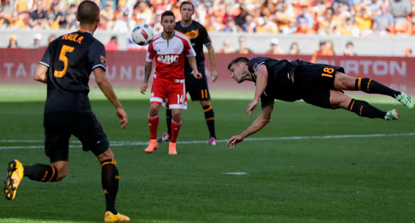 David Horst of Houston Dynamo clears the ball with a diving header against the New England Revolution.