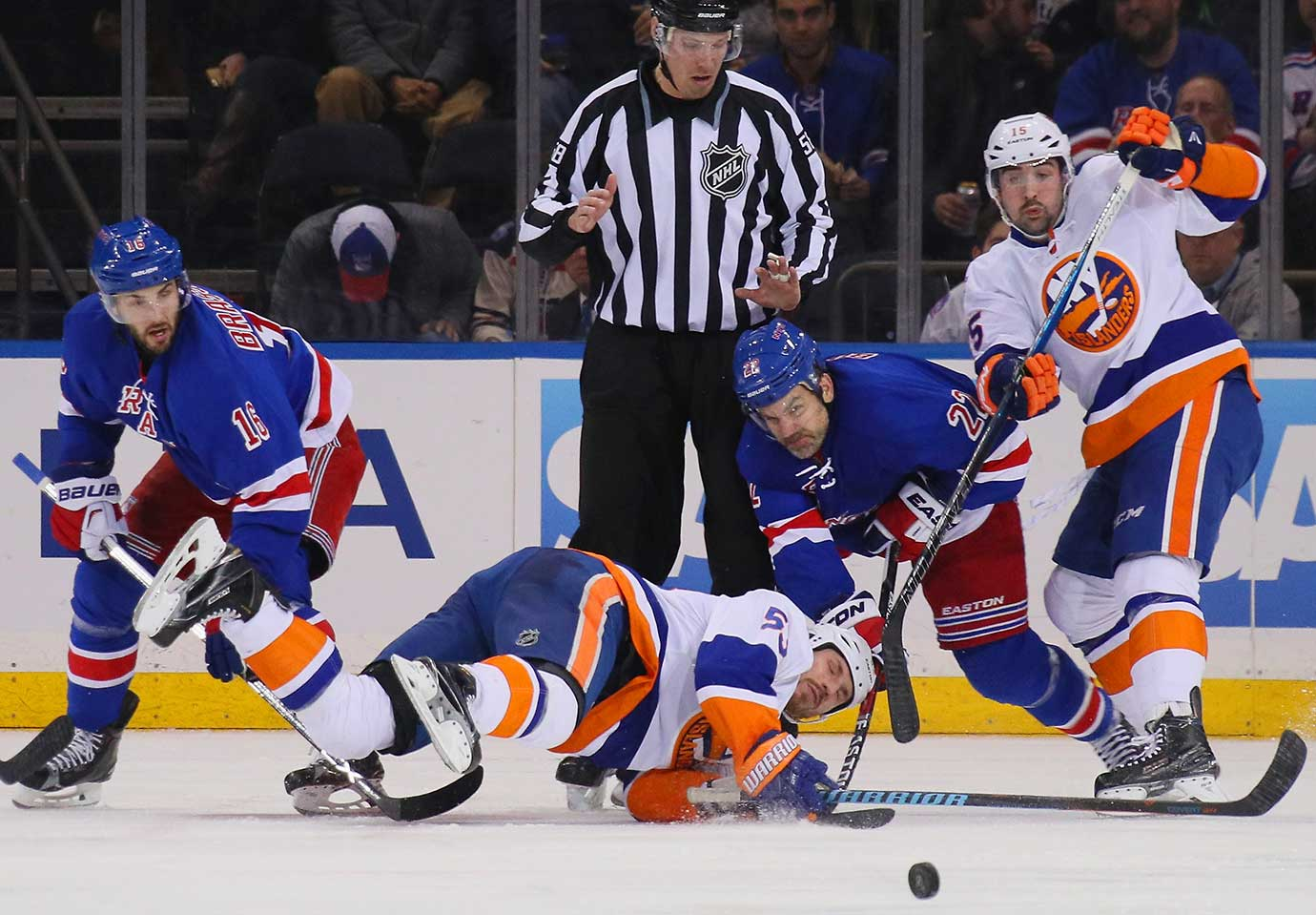 Casey Cizikas of the New York Islanders is tripped up during a faceoff against the New York Rangers.