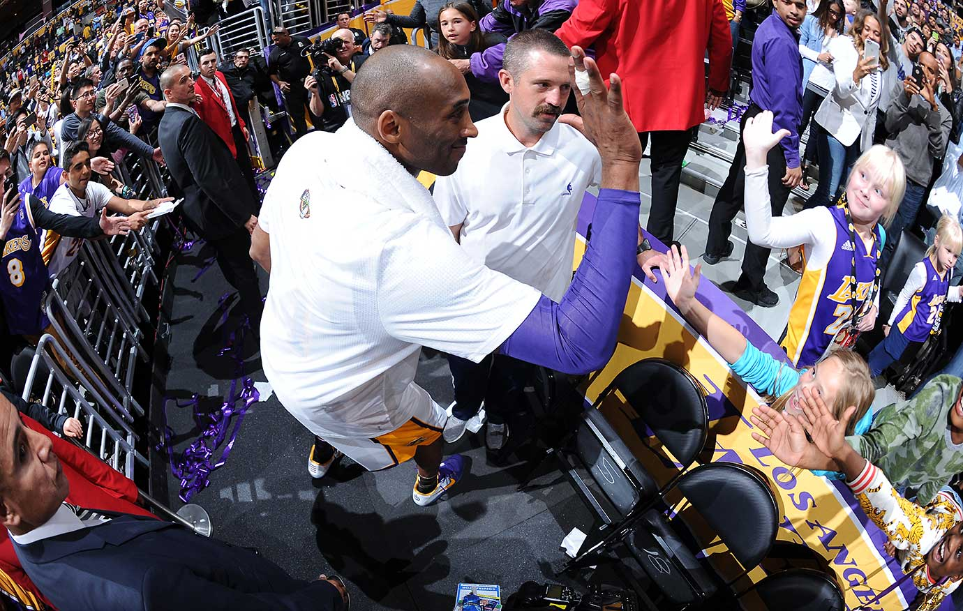 Kobe Bryant shakes hands with fans after the game against Golden State.