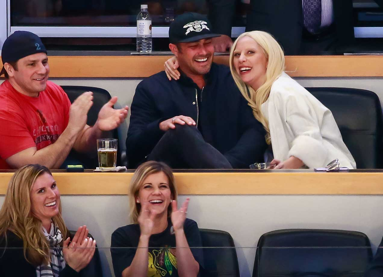Actor Taylor Kinney and Lady Gaga enjoy watching the NHL game between Chicago and Detroit at the United Center.