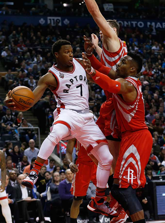 Toronto's Kyle Lowry looks to pass while being guarded by Houston's Dwight Howard and Donatas Motiejunas.