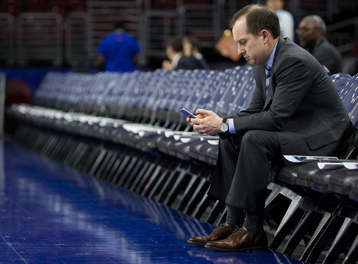 Philadelphia 76ers general manager Sam Hinkie looks down at his phone prior to the game against the Sacramento Kings.