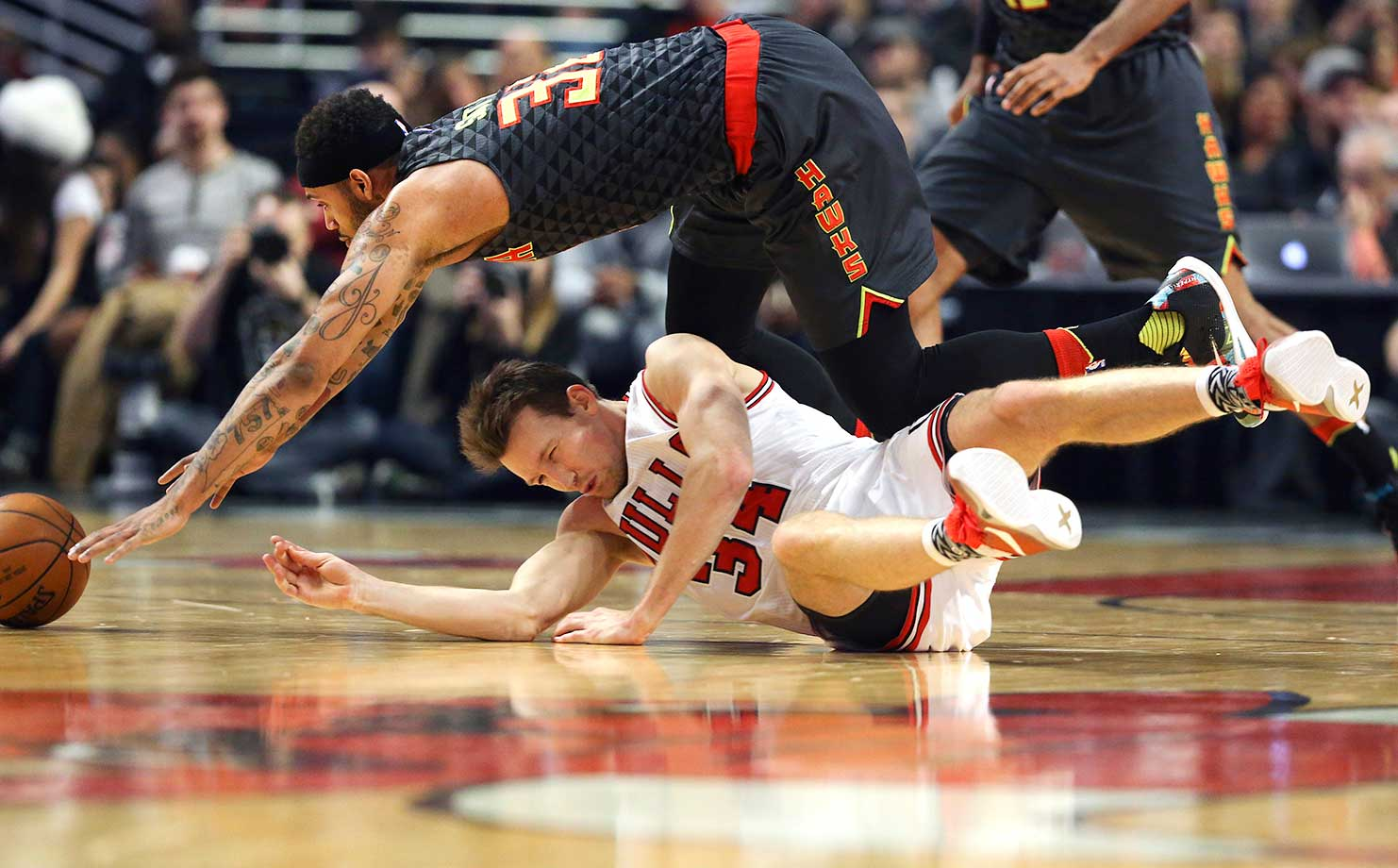 The Atlanta Hawks' Mike Scott climbs over the Chicago Bulls' Mike Dunleavy (34) to go after a ball.