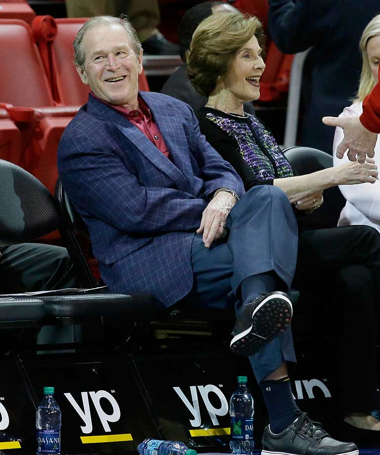 Former President George W. Bush sits with wife Laura before the SMU-Tulsa game in Dallas.