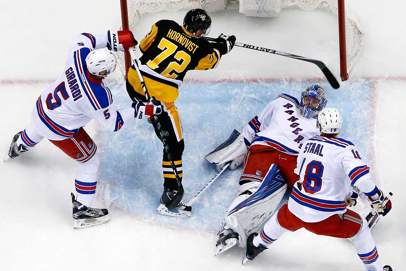 New York Rangers goalie Henrik Lundqvist lies on the puck in the goal crease with Patric Hornqvist looking for a rebound.