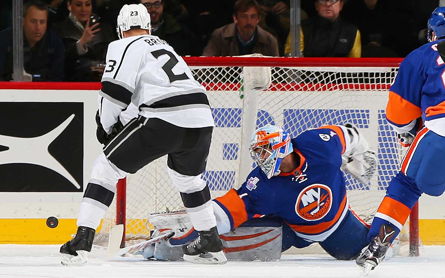 Thomas Greiss of the New York Islanders makes a save on Dustin Brown of the Los Angeles Kings.