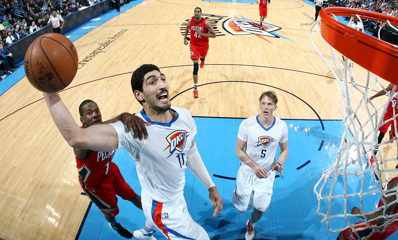 Here are some of the images that caught our eye on the sports night of Feb. 11, starting with  Enes Kanter of the Oklahoma City Thunder being held down somewhat by a New Orleans defender.