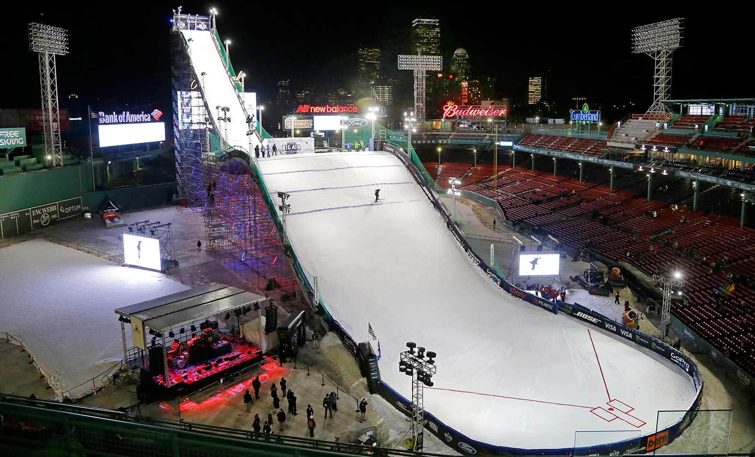 A worker paints a blue line on the ramp before the snowboarding competition of the Big Air at Fenway Park in Boston.