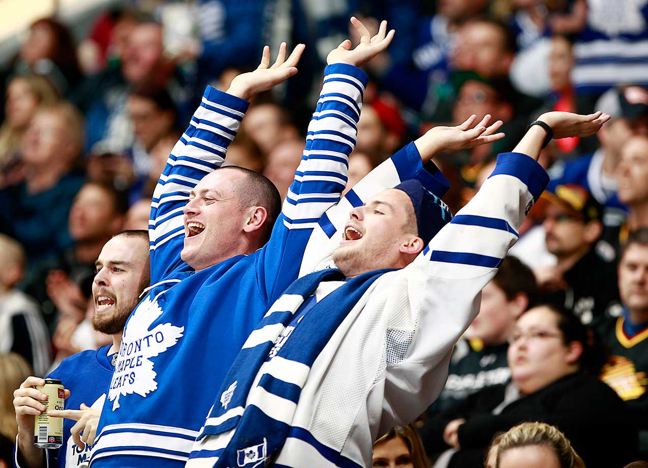 Two fans of the Toronto Maple Leafs celebrate a goal against the Vancouver Canucks.