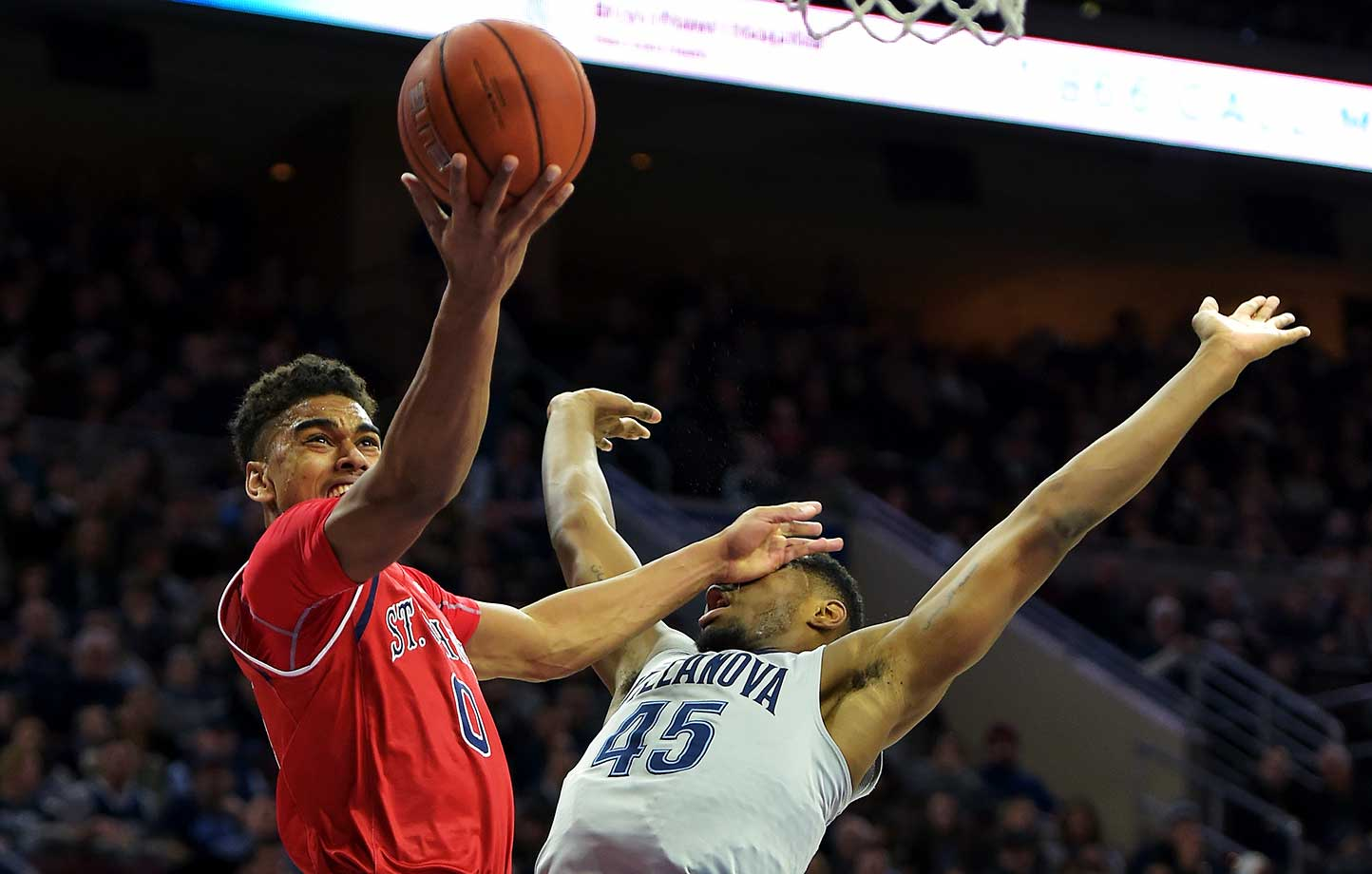 Malik Ellison of the St. John's Red Storm is fouled by Darryl Reynolds of the Villanova Wildcats.