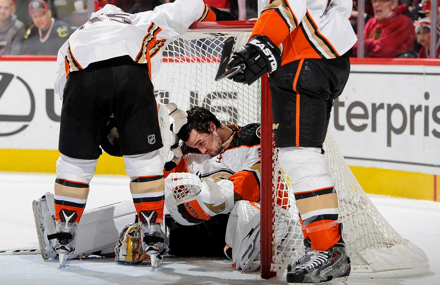 Goalie John Gibsonof the Anaheim Ducks sits in the net after taking a hit from the Chicago Blackhawks.