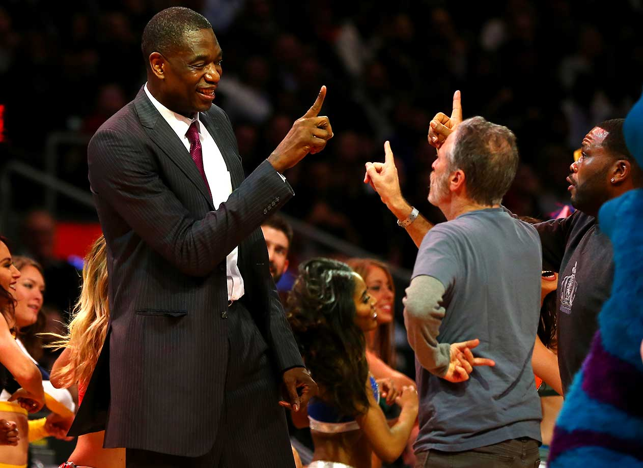 Former NBA player Dikembe Mutombo and TV personality Jon Stewart dance on court at NBA All-Star Weekend.