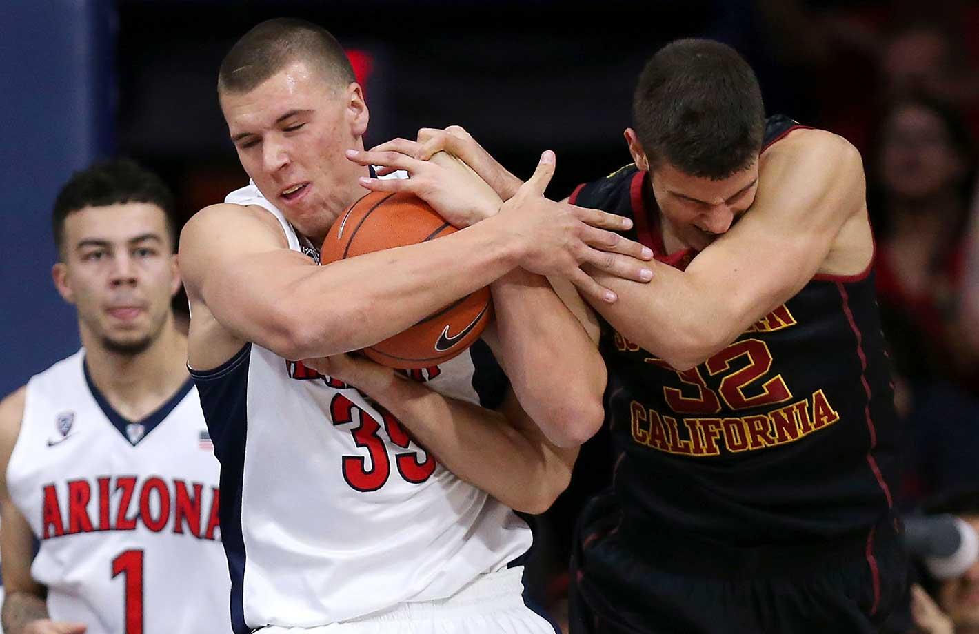 Kaleb Tarczewski of the Arizona Wildcats fights for a loose ball with Nikola Jovanovic of the USC Trojans.