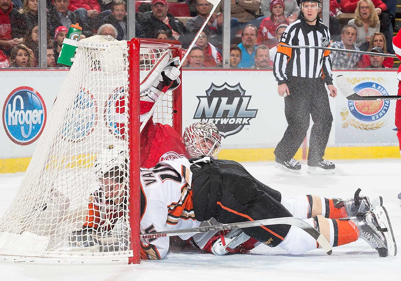 Sami Vatanen  of the Anaheim Ducks crashes into goaltender Jimmy Howard of the Detroit Red Wings at Joe Louis Arena in Detroit.