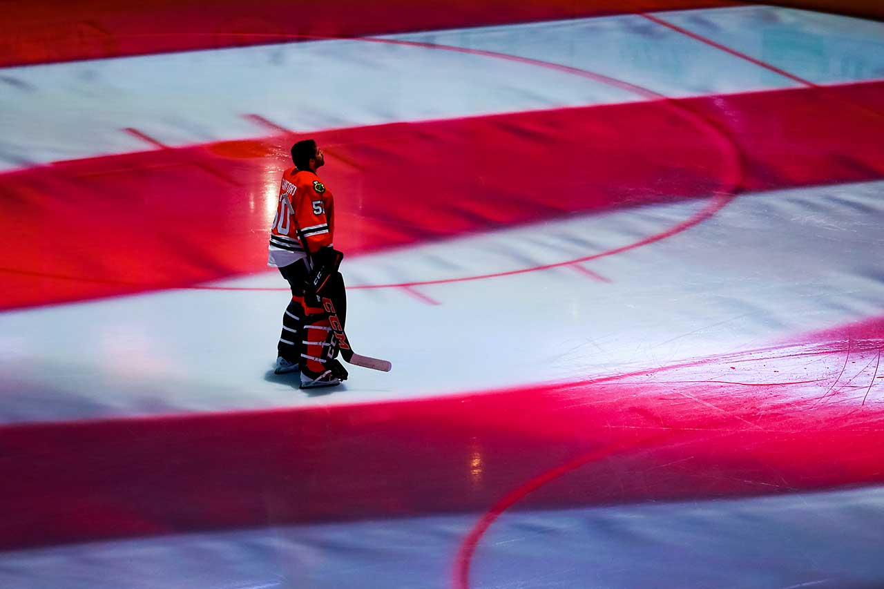 Goalie Corey Crawford of the Chicago Blackhawks stands on the ice during the national anthem prior to the start of the NHL game against the Montreal Canadiens.