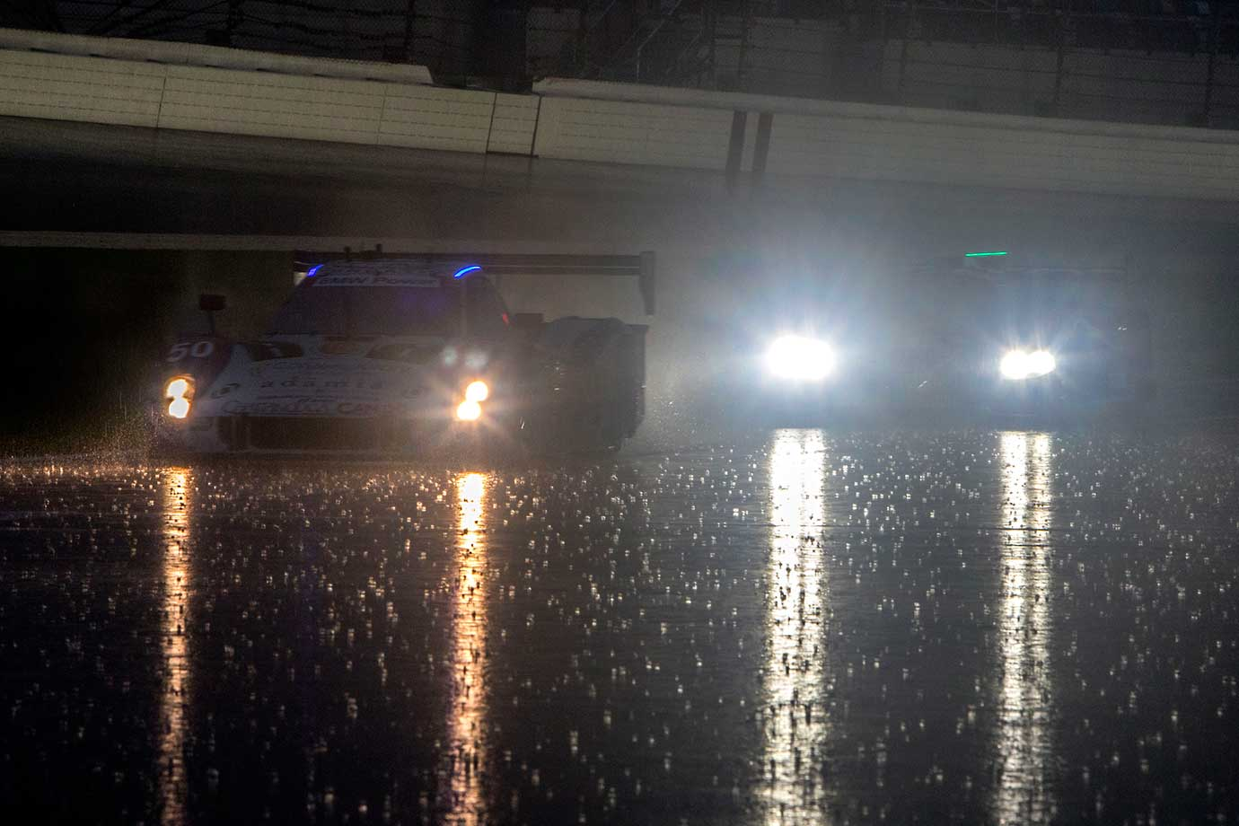 Cars drive on pit road in the rain during practice for the Rolex 24 at Daytona at Daytona International Speedway in Florida.