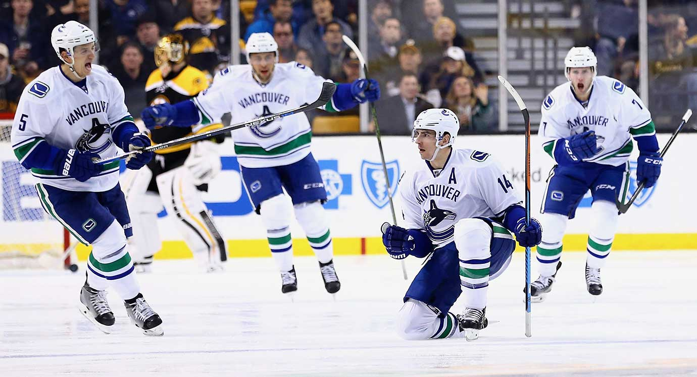Alex Burrows of the Vancouver Canucks, second from right, celebrates with Luca Sbisa (5) and Linden Vey (7) after scoring against the Boston Bruins at TD Garden in Boston, Massachusetts. The Canucks won 4-2.