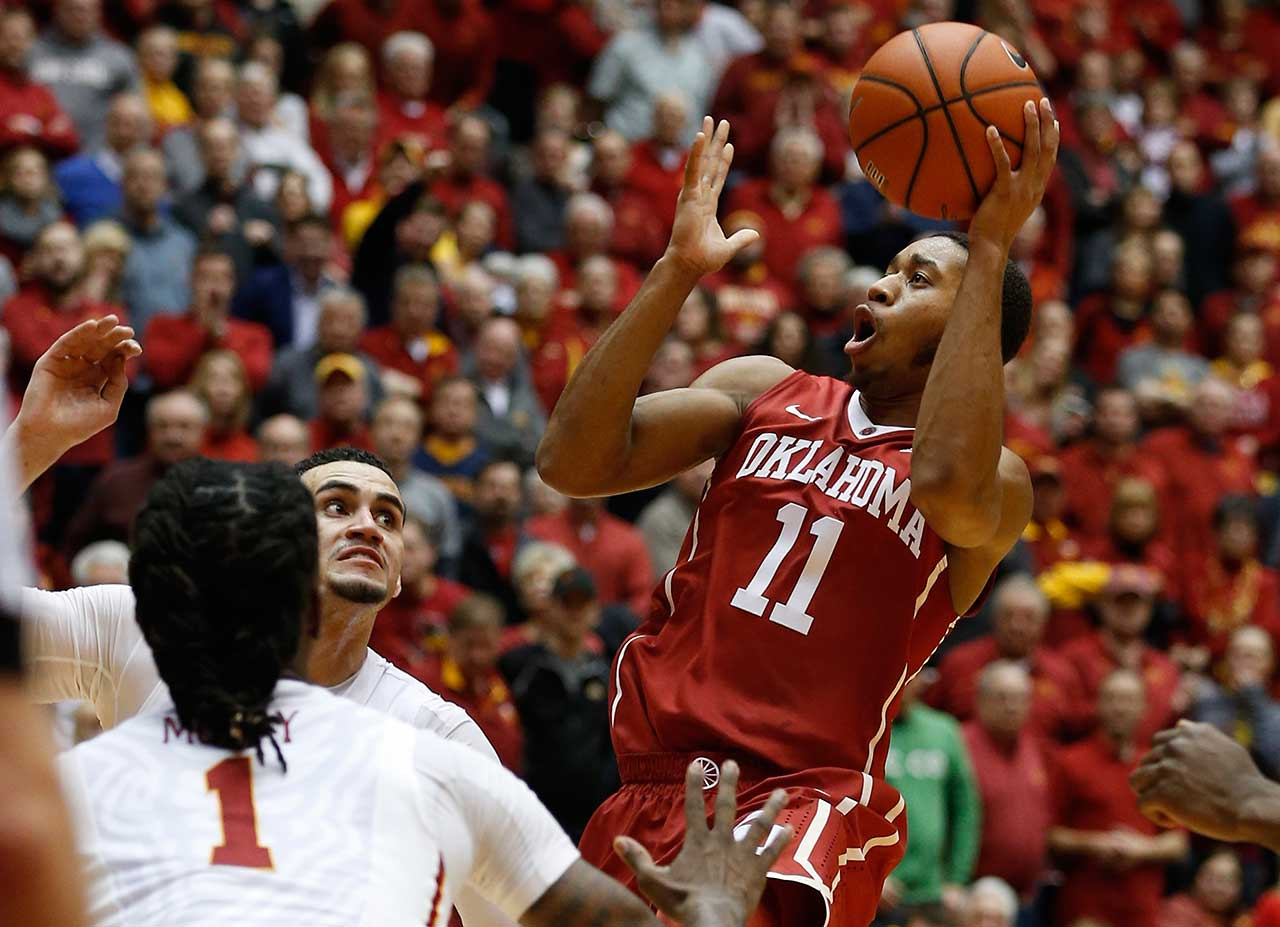 Isaiah Cousins of the Oklahoma Sooners takes a shot as Abdel Nader and Jameel McKay of the Iowa State Cyclones defend at Hilton Coliseum in Ames, Iowa.