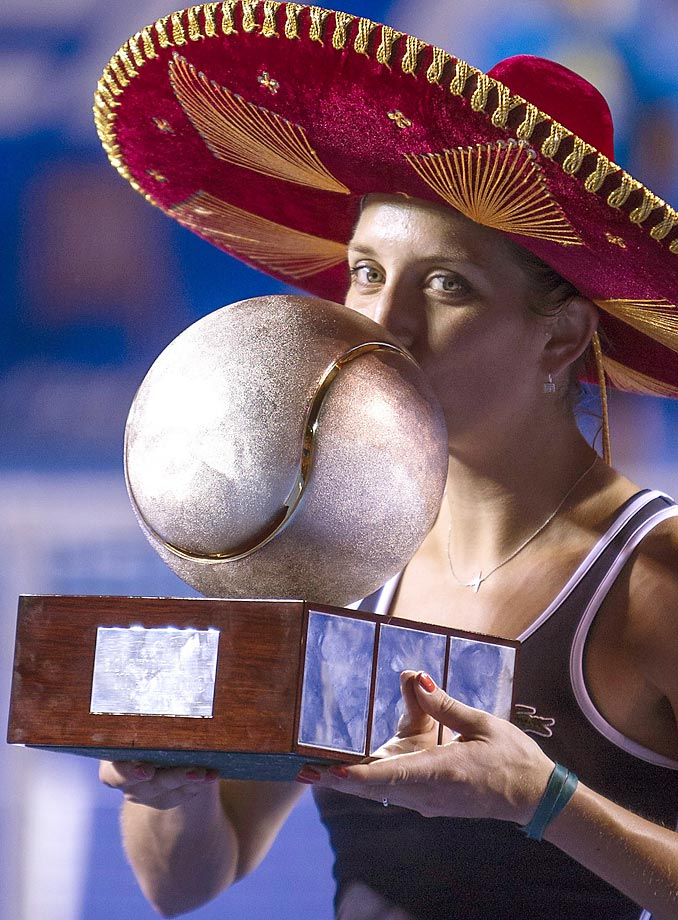 Timea Bacsinszky kisses her trophy after beating Caroline Garcia in the finals of the Mexico Open  tournament.