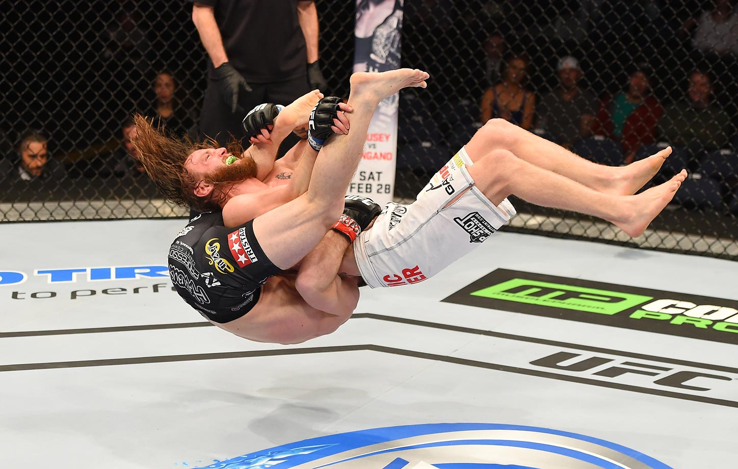 Timothy Elliott (right) jumps backward to take down Zach Makovsky in their flyweight fight during the UFC Fight Night event.
