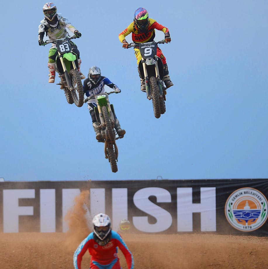 Motocross riders perform on the last leg of a race during the Turkey Motocross Championship.