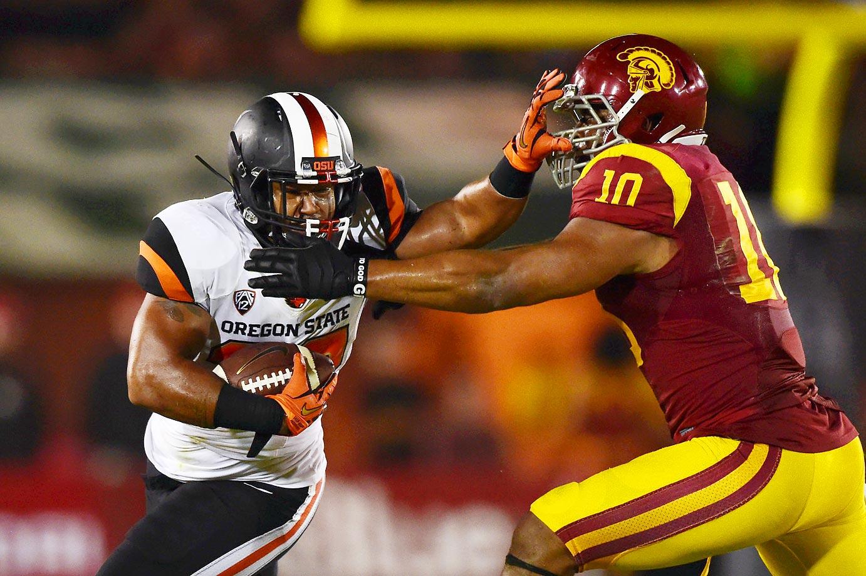 Oregon State fullback Tyler Anderson stiff-arms USC linebacker Hayes Pullard.