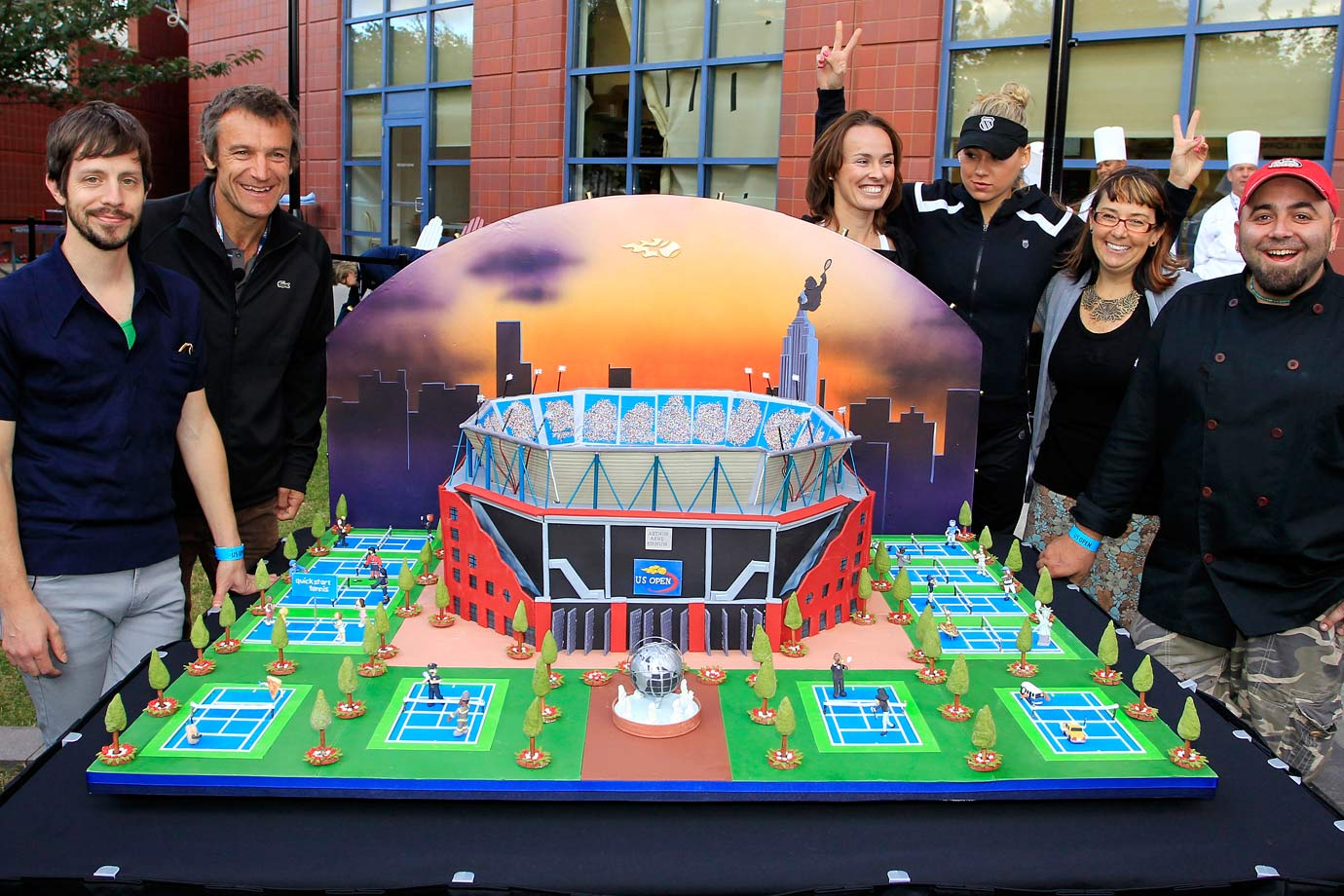Anna Kournikova and Martina Hingis pose with the bakers who made a replica of the USTA Billie Jean National Tennis Center, on display outside the real center on Sept. 9, 2010.