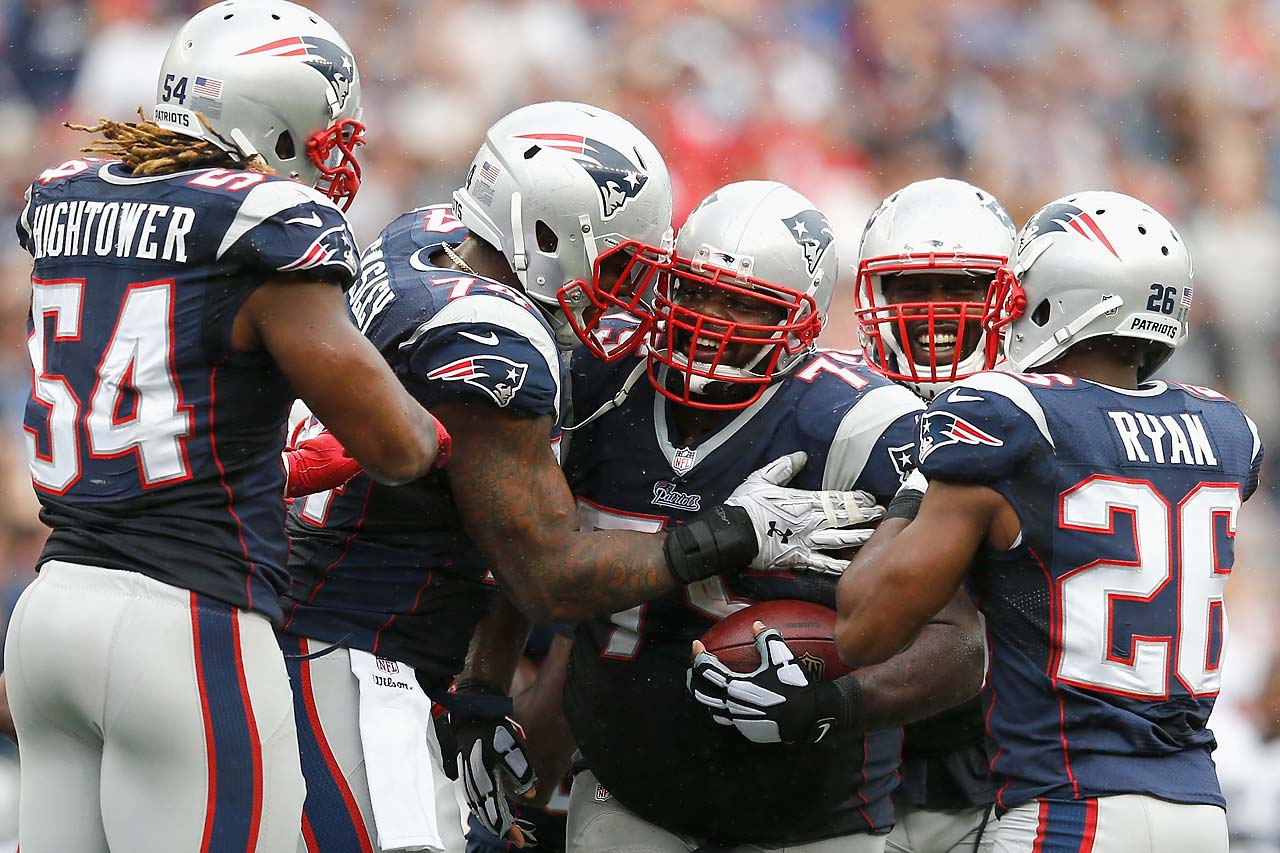 Vince Wilfork celebrates with teammates after intercepting the ball during the fourth quarter against Oakland.