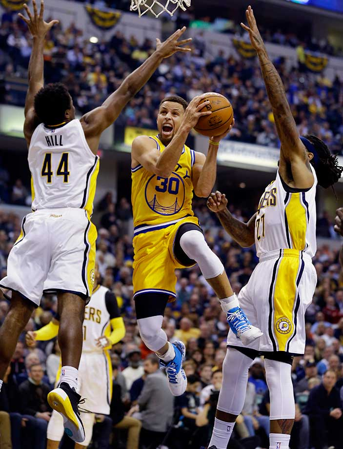 Steph Curry shoots between Solomon Hill (44) and Jordan Hill (27) of the Indiana Pacers.
