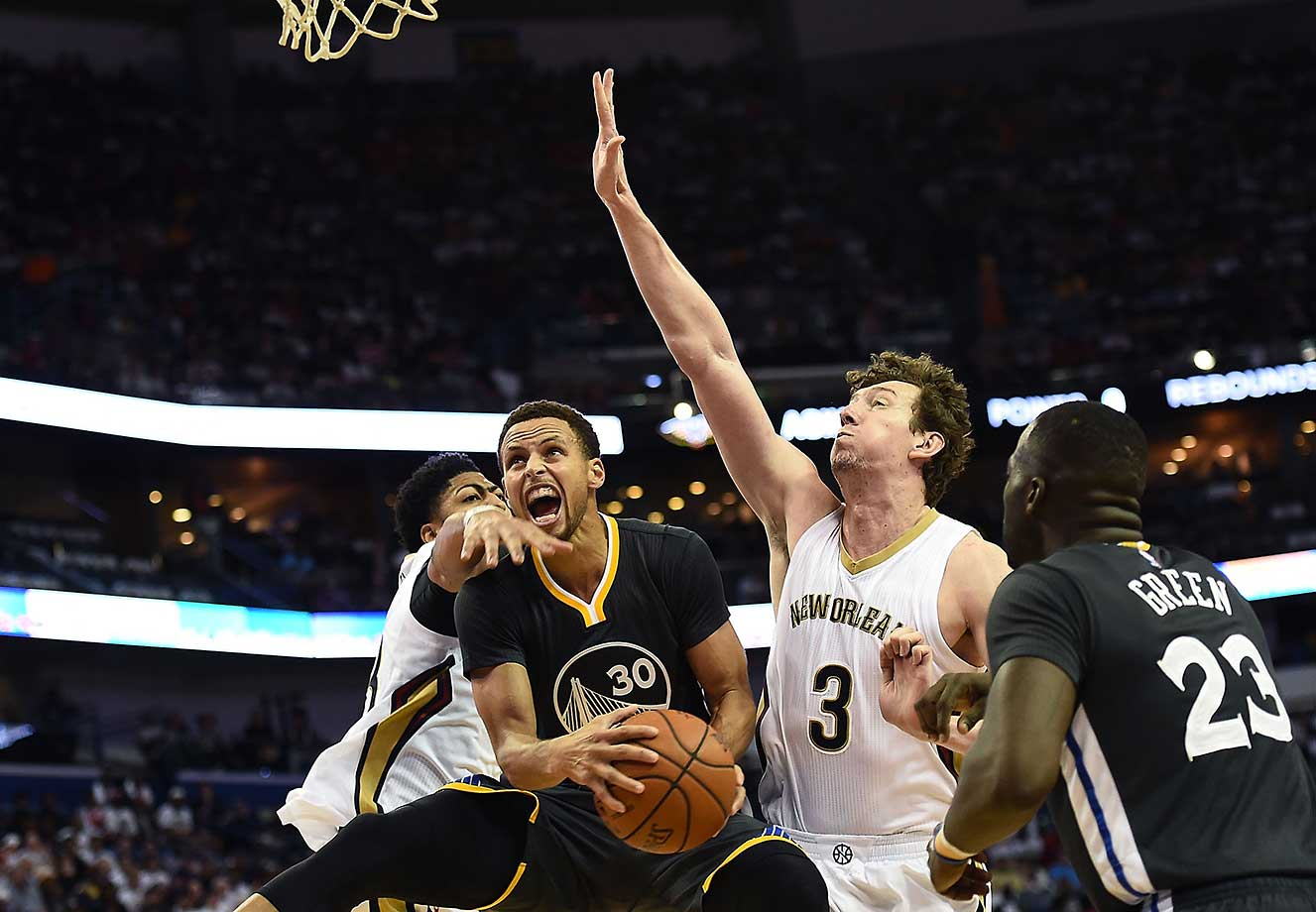 Steph Curry drives to the basket between Anthony Davis (23) and Omer Asik (3) of the New Orleans Pelicans.