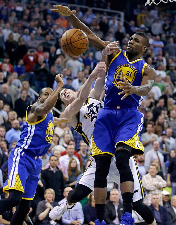 Center Festus Ezeli blocks the shot of Utah forward Gordon Hayward as Andre Iguodala looks on during a 106-103 victory.