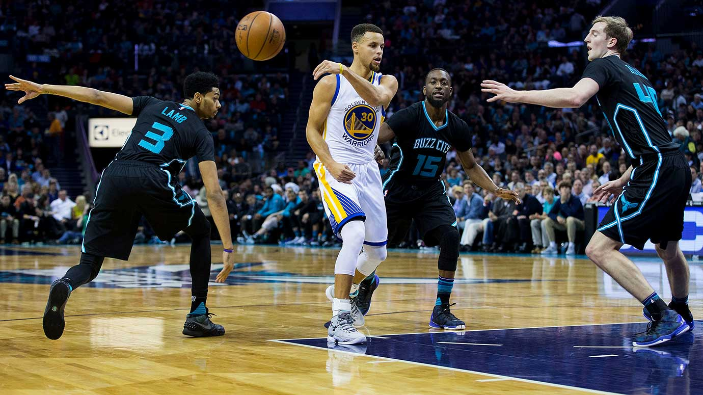 Stephen Curry makes a no-look pass while surrounded by Jeremy Lamb (3), Kemba Walker (15) and Cody Zeller of Charlotte.