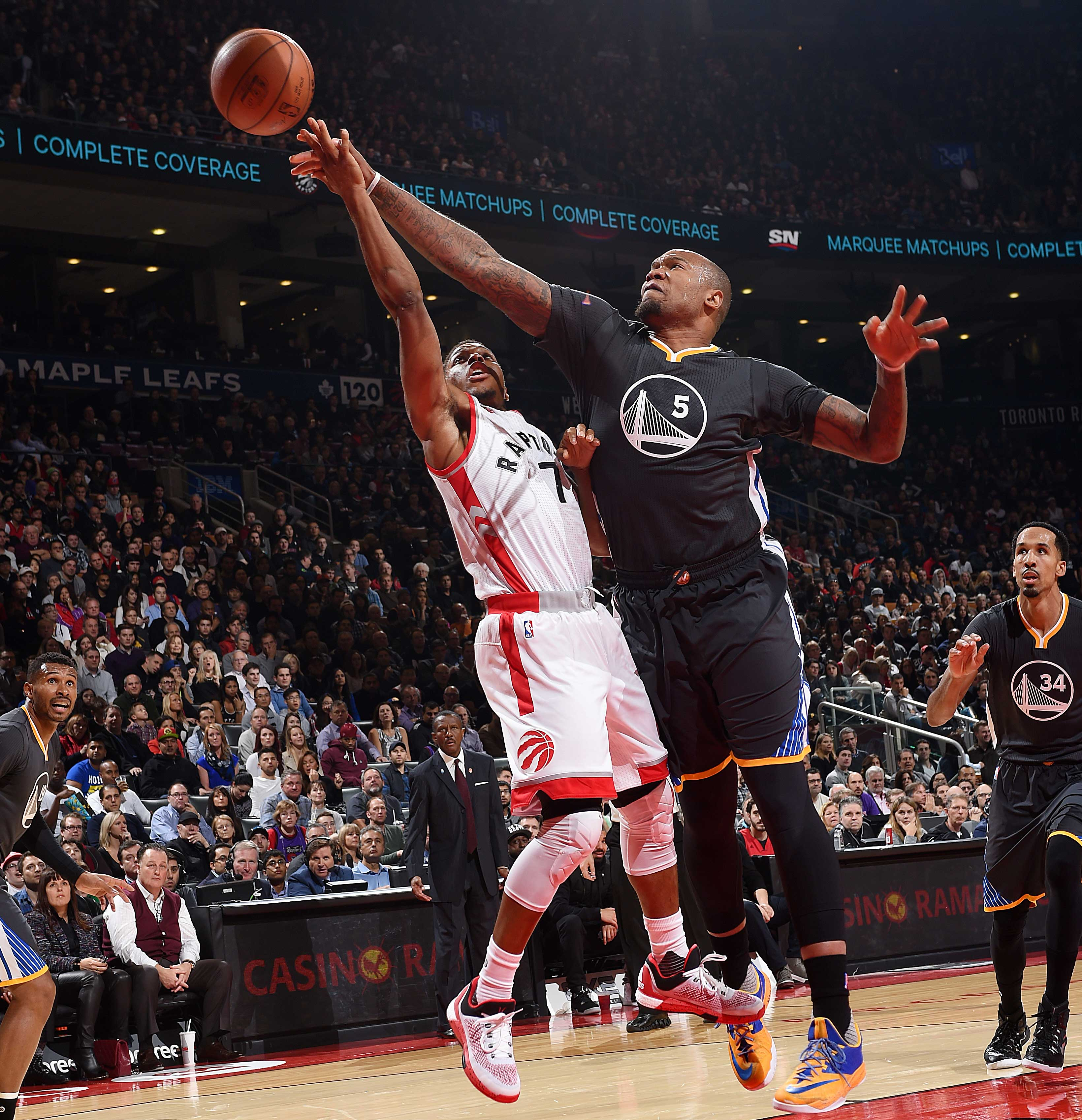 Marreese Speights of the Warriors blocks the shot of Kyle Lowry of the Toronto Raptors.