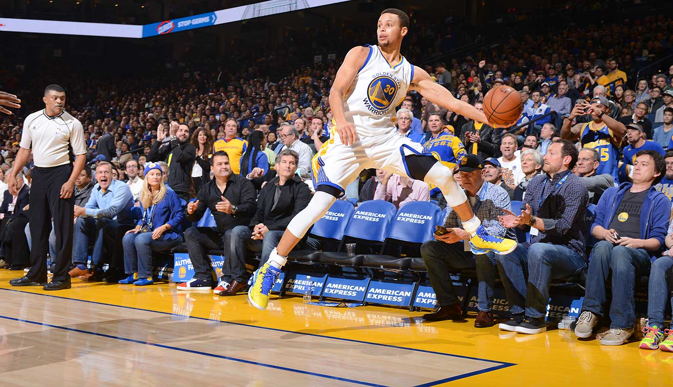 Steph Curry saves the ball from going out of bounds while facing the Milwaukee Bucks.