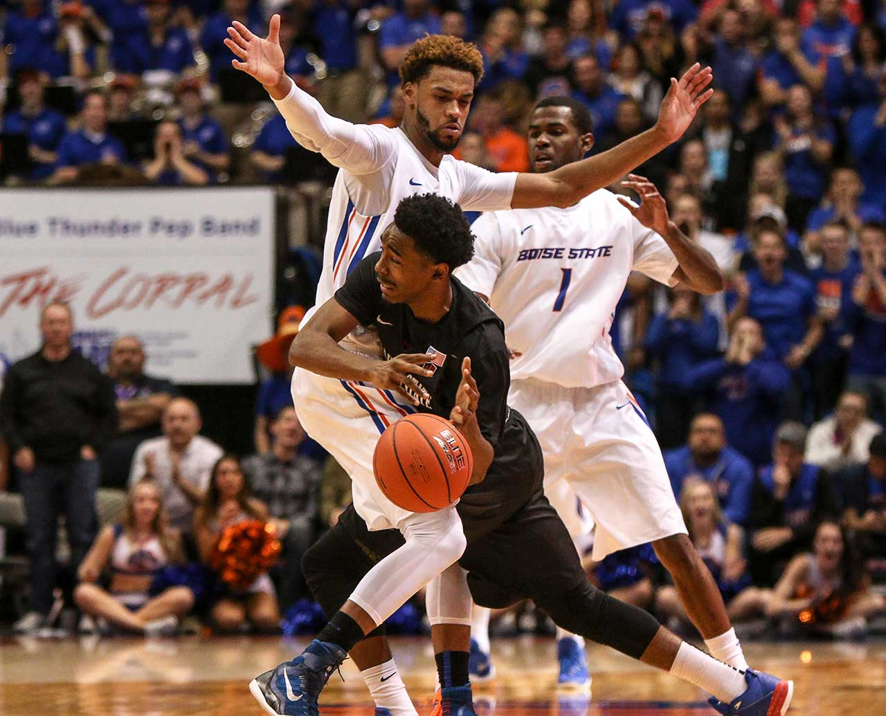 Guard Jeremy Hemsley of the San Diego State Aztecs turns the ball over due to the defense of forward James Webb III of the Boise State Broncos.
