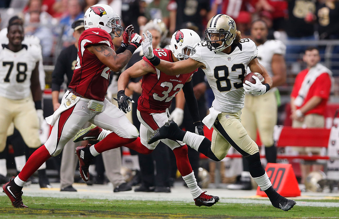 Wide receiver Willie Snead of the New Orleans Saints stiff arms free safety Rashad Johnson of the Arizona Cardinals.