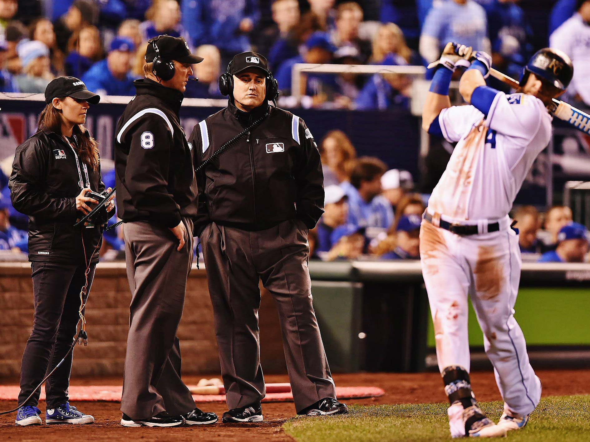 The officials await a replay ruling from the command center in New York on a close play at first. The call was reversed, resulting in an out.
