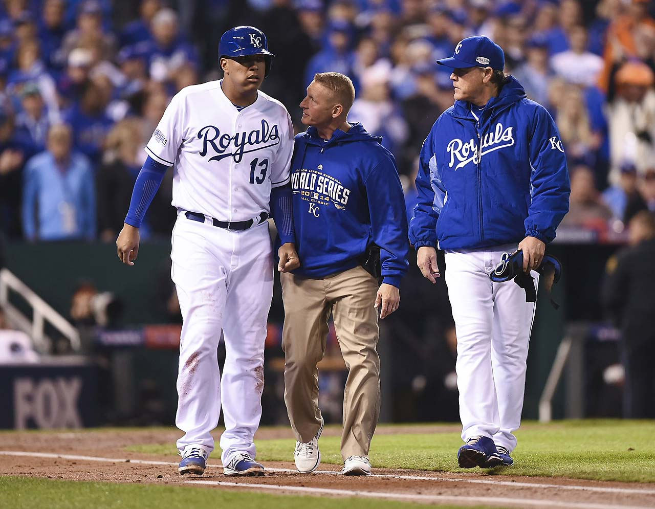 Perez gets escorted toward first base. He shook off the pain and remained in the game but was held hitless on the night.