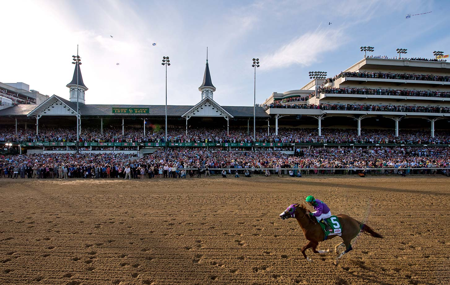 California Chrome, egged on by jockey Victor Espinoza, races past the grandstand and towards the finish line to win the 140th running of the Kentucky Derby.
